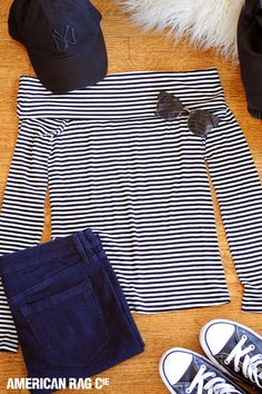 Black and white stripes never go out of style. Update them for the fall with this casual, but always chic look: an off-the-shoulder striped top, dark denim jeans, Converse and a baseball hat.