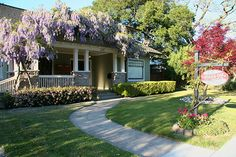 Hidden Oak Inn! Built in 1914 by Ralph E. Murphy, this large, two-story house has a high gabled roof and a front porch framed with Wisteria...