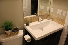 Bathroom Reno... this tiny bathroom looks very similar to the space we are working with for the boys!  Love the dark vanity with white top... the tile backsplash is nice too!