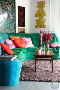 Sofá verde, pufe azul e uma profusão de cores nas almofadas para esse resultado moderno e vibrante. Veja mais no Blog Midá!