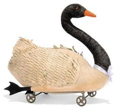 A STEIFF FELT BLACK-NECKED SWAN ON WHEELS, (2128), white, brown and black glass eyes, orange felt beak, black velvet neck, black feet, carded wings, wire frame with gold-painted cast metal wheels and small FF button, circa 1910 --13in. (33cm.) long (velvet worn, some discolouration)