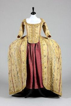 A fine gold brocaded striped silk robe à la Française, Italian or Spanish, circa 1770, with closed-front bodice and wide pannier sides with pocket slits, the silk woven with puce and silver bands within the textured cloth of gold stripes, Kerry Taylor Auctions