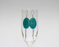 Adorned with fun silver tassels, the slightly shimmering leaf-shaped focal beads make cute and funky earrings perfect for many occasions. Intriguing and vibrant, these dangle earrings will perfectly accent your personality and style.  These green earrings belong to my Oh My Odd! collection of playful hanging earrings. Each pair in this collection is made in just one copy, so these fun dangles will be for your ears only. Or for the ears of that one special woman, as they will be a charming…
