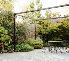 Brian and Trish Perkins' mixed low maintenance shrub and perennial planting soften the boundaries of the slate paved courtyard. Tio Collection dining table and chairs by Mass Productions. Photo by Annette O'Brien. via The Design Files. Diy Pergola, Building A Pergola, Pergola Canopy, Pergola Swing, Outdoor Pergola, Wooden Pergola, Pergola Shade, Pergola Ideas, Outdoor Patios