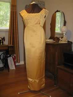 The 1960's in a gold satin column gown.
