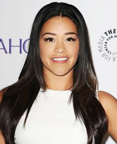 Gina Rodriguez with a sleek and straight center-parted blowout, and glowing, natural makeup