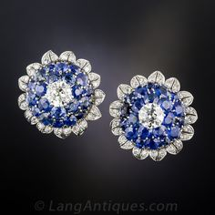 A bright white pair of European-cut diamonds, weighing one carat each, crown these bold and beautiful sapphire and diamond sunflower motif earrings. The center stones sparkle atop domes of gorgeous electric blue sapphires which, in turn, are encircled by twinkling diamond-set petals. Expertly hand-fabricated in platinum during the late-1930s -1940s. These chic and impressive ear baubles measure just over 7/8 inch across. Posts with mega backs.