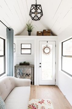 Inside the Lindley tiny house you'll find a futon in the living area to serve as a guest bed, a bedroom loft with double dormers, and white oak flooring.