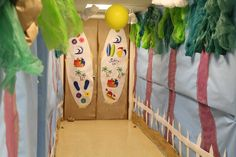 Surf Shack Path! Cover walls with blue butcher paper. Paint the palm tree trunks using two different colors of brown to make it more dimensional.  Staple decorator fabric in different shades of green for the leaves.  Use various type of fabric or decor mesh to create the green for leaves/branches. cokesburyvbs.com