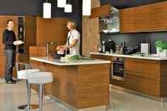 Kuchyně LINE v provedení dýha americký ořech, mat má jednoduché řešení moderní kuchyňské linky, praktické vysoké potravinové skříně, barové sezení (barová židle MIDJ – Bongo), osvětlení pracovní plochy je integrované do horních skříněk.