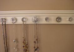 jewelry/necklace  holder organizer with 7 decorative cabinet knobs featuring large rhinestone center on off white background 20  inches long. $38.00, via Etsy.