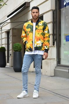 A statement bright print quilted bomber jacket with skinny acid wash jeans and Stan Smith trainers