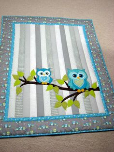 Owl Baby Quilt  Whoooo wouldnt love to cuddle with this adorable baby quilt?? It would be a perfect gift for either a baby boy or a girl, infant or toddler. It measures a generous 37 x 47 inches.  I personally designed, pieced and quilted this project, making it a unique heirloom keepsake for that special baby in your life!  The front was created from a variety of shades of white and grey strips. Numerous shades of aqua were used to create the two little owls sitting on a leafed branch. They…