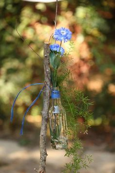 Rustic aisle decoration - bottle filled with wildflowers and tied to a stick!