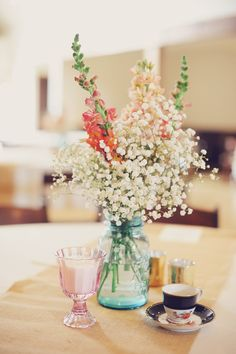Baby's breath with a little pop of color. Dusty miller and a peach garden rose