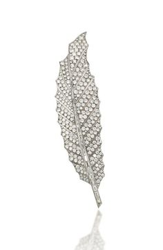 A DIAMOND FEATHER BROOCH The spine set with a tapering row of baguette-cut diamonds, to the pavé-set brilliant-cut diamond shaped surround, 12.9cm long, double prong fitting Signed Raiola