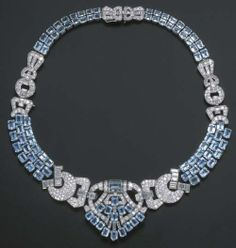 "1930  Art Deco Diamond and Aquamarine Necklace by Lacloche Frères.    ""The front palmette panel with pavé-set diamond buckle shoulders to a three-row rectangular-cut aquamarine band and diamond and aquamarine backchain, circa 1930, 41.5 cm. long, with fittings for a brooch and tiara, and also converts to a bracelet, in original blue leather fitted case by Lacloche Fres"", London -- description from Christies.com"