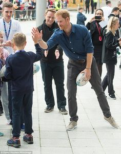 Harry high fives a young competitor after changing into casual shoes for an informal game ...