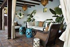 Chic Patio Deck Design with Outdoor Cane Furniture, Turquoise Blue Garden Stools, and Moroccan Pendants Chandeliers.