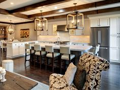 This living room and dining area connect to an open-concept kitchen where two large rustic lanterns are a standout feature above the kitchen island.