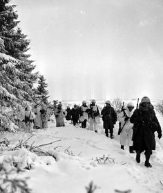 American Infantrymen trudge through the snow as they march along the edge of a woods near Iveldingen (Amel), in the driver to recapture Sankt-Vith, 20 january 1945.