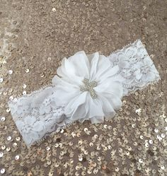 This listing is for a fabric flower headband. Flower is made of white fabric and rhinestone cross is an extremely sparkly bling accent. Flower
