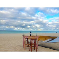 Romantic beach setting with an old table two stools a bottle of wine and a home cooked meal