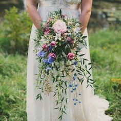 A gorgeous relaxed outdoor wedding in a meadow with rustic styling and a gorgeous cascading wild flower bouquet.