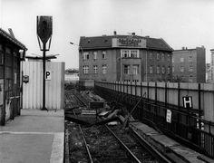 Der heutige S-Bahnsteig an der Friedrichstraße ist im April 1990 in Richtung Westen noch abgesperrt, sichtbar hinter dem Haltesignal. Hinter der Absperrung ist noch das Dach des Grenzturms für die Grenzpolizei zu sehen.