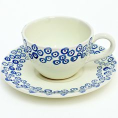 White ceramic coffee cup with saucer, decorated with a dark blue target design on both the cup and the saucer. Click on the image to learn more about this beautiful coffee cup.
