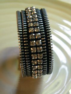 This zipper bracelet has been constructed using recycled vintage zippers. The rhinestones have been hand sewn on and the bracelet closes with a magnet