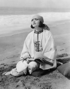Negri reading on beach. Pola Negri (1897-1987), born in Poland Apolonia Chalupec, was a stage and film actress who achieved worldwide fame for her tragedienne and femme fatale roles from the 1910s through the 1940s during the Golden Era of Hollywood film. Negri was the richest woman of the film industry at the time, living in a mansion in Los Angeles modeled after the White House. She started several ladies' fashion trends, including red painted toenails, fur boots, and turbans.