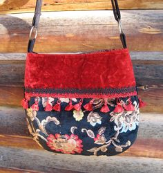 This is a fun bag. It is made of vintage crushed red velvet upholstery fabric and a velvet print tapestry fabric with a red fringe and black fine corduroy adjustable cross body strap. The details are: Size: 15 inches wide x 13 inches high Bag fabric: Cotton polyester crushed red velvet and printed velvet upholstery with a 2 inch red coloured fringe on the front. Back is black velvet upholstery fabric. As this is vintage fabric, there is a minor 1/2 inch by 1/4 inch wear on the fron...