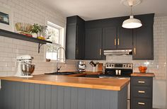 dream kitchen. White subway tiles, dark cabinets, wood countertops.