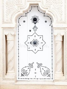 Photo about Arab white door with hands of fatima in Tunisia to Mahadia, richly ornamented and drawn with arabesques. Image of ornamented, morocco, classic - 107437789