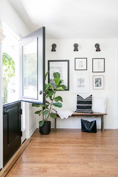 a welcoming entryway moment at the home of eden passante with sconces, artwork, bench and fiddle fig. love the half door too! | sugar + charm