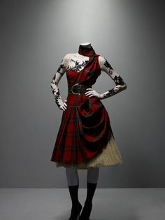 * Alexander McQueen (British, 1969–2010). Ensemble Widows of Culloden, autumn/winter 2006–7. Dress of McQueen wool tartan; top of nude silk net appliquéd with black lace; underskirt of cream silk tulle. Photo Sølve Sundsbø