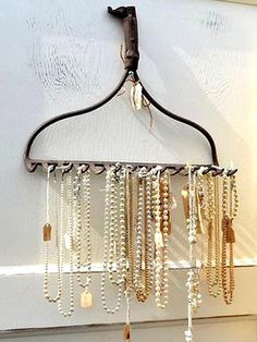 A rustic (or rusty!) rake head re-purposed to hold delicate strands of pearls is shabby chic at its finest.