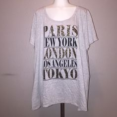 """Lane Bryant City Tee Very comfy gray tshirt with printed city names on front. """"Paris"""" """"London"""" and """"Tokyo"""" a embellished with glitter drops for some added sparkle! You can easily dress this shirt up with a nice blazer or wear it over jeans for a casual chic look. Lane Bryant Tops Tees - Short Sleeve"""