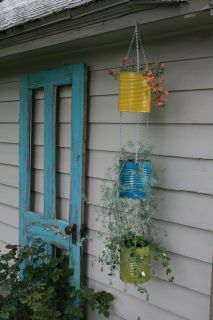2 IDEAS: 1-Recycled cans put to good use as pots for hanging plants 2-An old wooden door against a blank wall in the garden with flowers, vegetables or shrubs planted in front