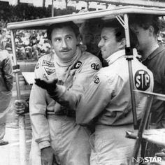Graham Hill and Jim Clark share an impromptu shelter at Indianapolis.