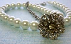 A pretty vintage silver and rhinestone bracelet link creates an asymetrical focal point for this classic, white pearl and antiqued silver chain necklace. $30