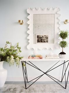 "source: Lonny Magazine      Michelle Adams - Watery blue walls paint color, Oly Studio George Console Table, Ballard Designs Atoll Rectangular Mirror Antique Glass, topiary and Holtkoetter Up-Down 5 1/4"" Wide Polished Brass Wall Sconces"