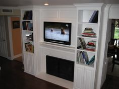 tv over fireplace and cabinets