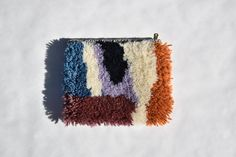 Fuzzy, hand-knotted clutch. Measures approximately 9x8 Outer fabric is cotton and wool. Lining is 100% cotton drill. Brass zipper. INSTAGRAM: h.f.james