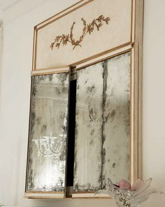 The mirror is actually a cover for a flat screen TV! The antique glass doors pull back to reveal the screen so you can hide it when you want to entertain.