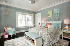 A feminine bedroom that coveys a message of comfort and peace. A cool combination of grey and light blue along with the zigzag rug over dark floor makes this room even more lively.