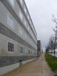 Herzog & De Meuron   Residencia Estudiantil Antipodes   Dijon, Francia   1992   Organizado como conjunto de unidades lineales situadas a lo largo de una espina de circulación con grandes galerias abiertas. Los muros exteriores están formados por muros in-situ de hormigón tintado y paneles prefabricados de hormigón ligero con carpinterías de aluminio. Todas las unidades son similares y las ventanas son todas iguales. El campus universitario sigue el modelo de edificios aislados en el parque