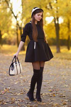 Czarny rozkloszowany płaszcz, kapelusz z kokardą i czarne kozaki za kolano