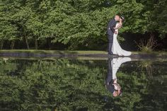 Clearwell Castle Wedding - Bride and Groom by the pond at Clearwell Castle with their reflections in the water